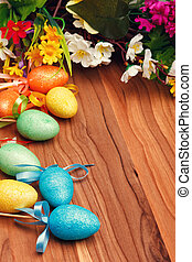 Easter flower arrangement and colorful eggs on wooden...