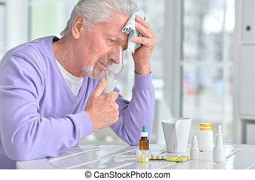 Elderly man doing inhalation - Portrait of an elderly man...