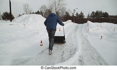 black shovel cleans snow white snow. man cleans a black...