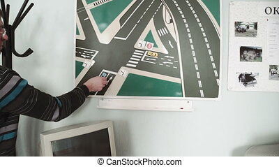 Class driving school, road signs, teacher man wearing glasses lectures a class Shows a road situation with two cars on the road junction