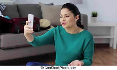 woman with smartphone and travel stuff at home - vacation,...