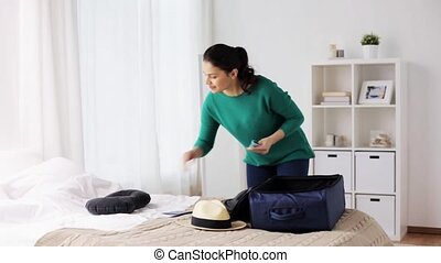 woman packing travel bag at home or hotel room - tourism,...