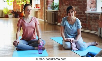 group of women resting on yoga mats in gym - fitness, sport...