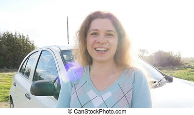 Young woman showing key to a new car - Young woman showing...