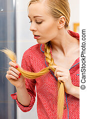 Blonde woman looking at her hair ends - Haircare and...