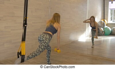 Sexy young beautiful girl doing fitness exercises in the gym.