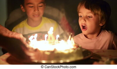 Happy kid blowing candles at his anniversary - Happy kid...