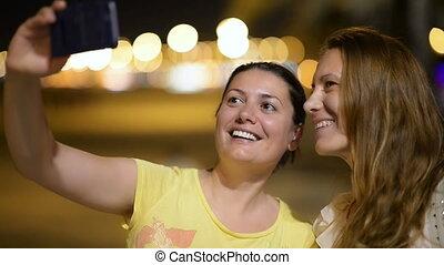 Young women enjoying night tourism - Young women taking...