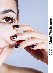 Beautiful glamour young woman with black nails and gold eyeshadows.