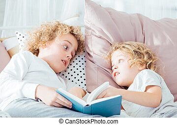 Boy reading book to brother - Boy reading book to his...