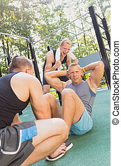 Man doing sit-ups while exercising with friends at park