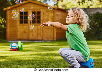 Small boy playing in garden during summer day