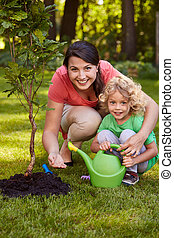 Mother and son watering tree