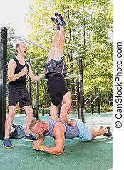 Men doing plank and headstand - Men exercising together...