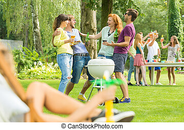 Young people grilling in garden