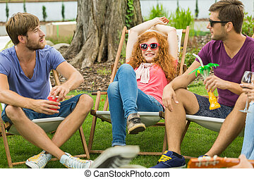 Friends relaxing on deckchairs during sunny day