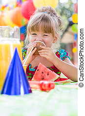 Girl eating muffin during party