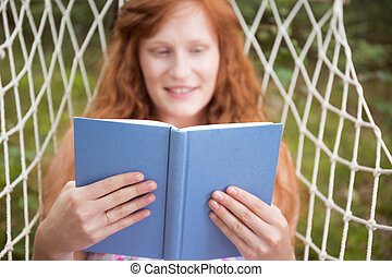 Smiling woman reading on a hammock