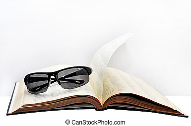 Open book with glasses.