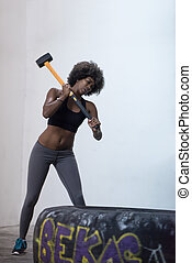 black woman workout with hammer and tractor tire -...