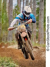 Motocross driver jumping with the bike at high speed on the...