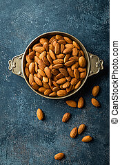 Almond nuts on dark background directly above copy space...