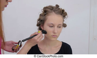 Professional make-up artist applying powder to woman's face...
