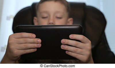 The boy in a leather chair with a tablet in his hands
