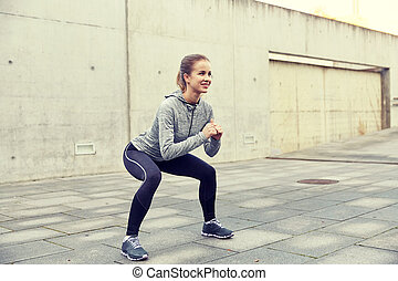 happy woman doing squats and exercising outdoors
