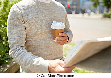 senior man with coffee reading newspaper outdoors - old age...