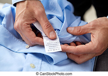 hands with shirt and care instruction label - clothes,...