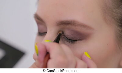 Professional make-up artist applying eyeshadow -...