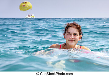 Girl 19 years old, swims in blue sea water alone.