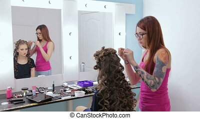 Hairdresser finishing hairstyle for teen girl - Hairstylist,...