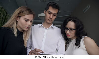 Two women and a man looking at the screen with the tablet...