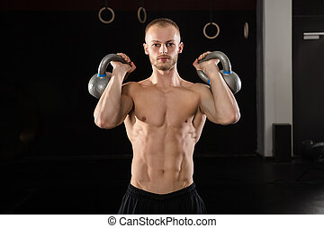 Man Exercising With Kettle Bell - Portrait Of A Young...