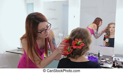 Hairstylist, hairdresser finishing creative hairstyle with flowers for teen girl