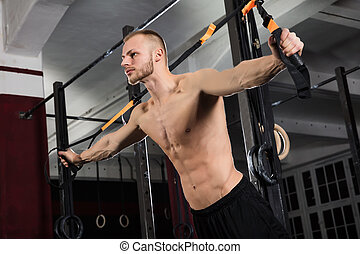 Man Exercising With Suspension Trainer