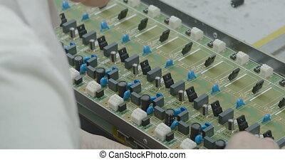 Manuall assemble parts on PCB. Closeup - Worker manually...