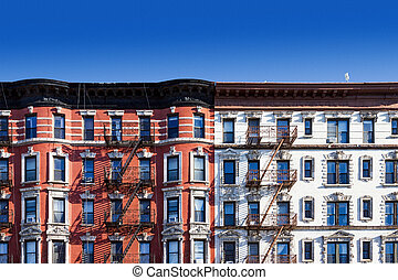 Block of old buildings in New York City with blue sky...