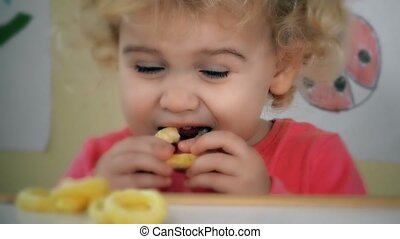 little girl eating corn circle sitting near table wit toys and drawings on wall