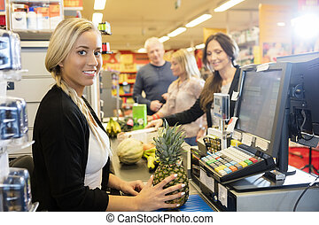 Cashier Holding Pineapple At Checkout Counter In Supermarket