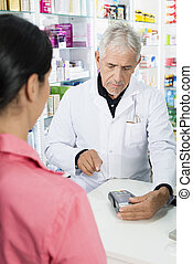 Chemist Swiping Card By Customer At Counter - Senior male...