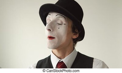 man MIME talking on an imaginary mobile phone over white...