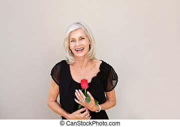 beautiful older woman laughing with red rose in black blouse