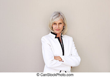 beautiful older woman staring and standing with arms crossed