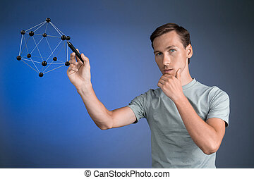 Young man works on a model of molecule. - Young man works on...