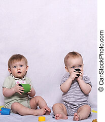 Little baby boy and toddler girl playing with toys