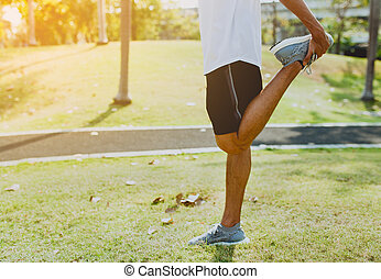 Athletic young man doing sport exercises at public park ,...