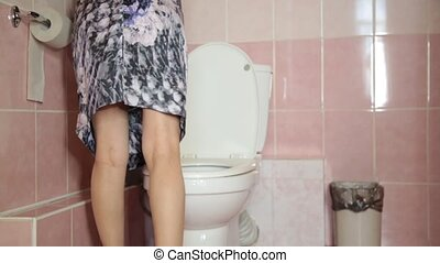 woman Using a Toilet like a man.